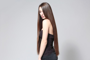 Wall Mural - Beautiful young woman with long straight hair on light background