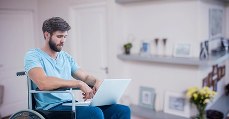 Man sitting on wheelchair and using laptop