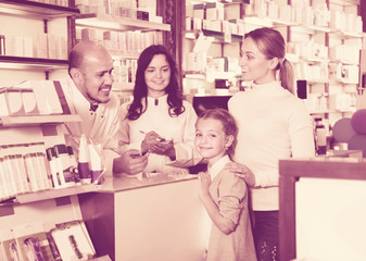 Two pharmacists helping customers