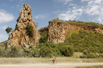 The tourist is cycling at the foot Stark rock towers in the Hells Gate National Park in Kenya