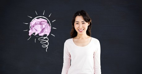 Woman standing next to light bulb with crumpled paper