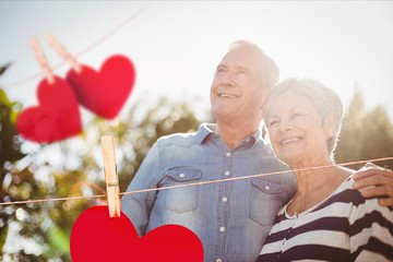 Red hanging hearts against senior couple in background