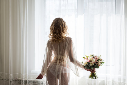 Bride near the window in her underwear. Blond sexy female Boudoir photo back to camera in front of large window. Bridal bouquet in the hand of bride.