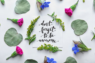 """Inscription """"DON'T FORGET TO BE AWESOME"""" written on paper with flowers and leaves on white background"""