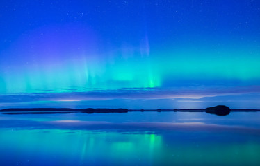 Northern lights dancing over calm lake (Aurora borealis)