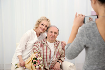 Young woman taking picture of happy senior couple at home