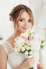 Gorgeous bride with broad smile holds wedding bouquet before her face
