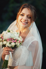 Blonde bride smiles tender standing in the rays of evening light