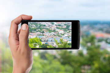 hand taking picture at the Mountain village in Thailand with a smart phone