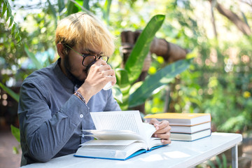 Handsome young man drinking coffee while reading book at home garden.