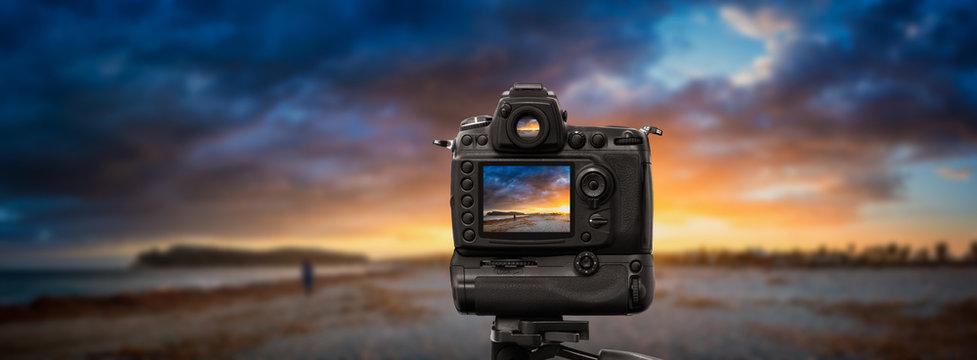 DSLR camera on tripod shooting seascape sunset