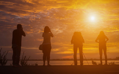 Group of people standing in an open field watching the sunse