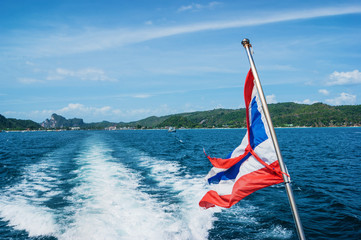 The national flag of thailand on the stern of the boat and the view of the wake