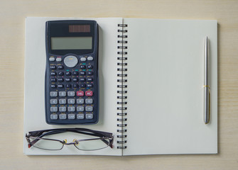 Top view eyeglasses,calculator and silver pen on spiral notebook of Office desk.