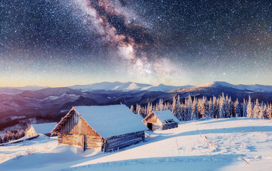 chalets in the mountains at night under the stars. Magic event in frosty day. In anticipation of the holiday