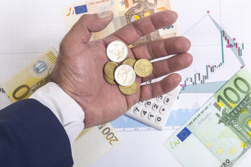 Concept of stock exchange trading profits. Stock market prices charts, 100,50,200 euro bills and calculator on the diagram. Businessman hand in suit with euro cents and euro coins. Macro image.