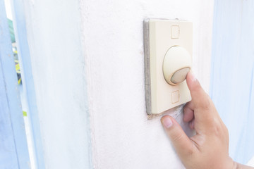 Female Hand Pushing the Doorbell Buzzer, front of house. The visitor hand presses the bell at the door