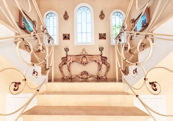 Luxurious staircase with marble steps and decorative and  ornamental iron railings. On the top are decorating furniture in neoclassical style, a table with candles.