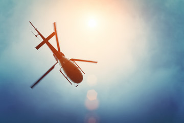 Wall Murals Helicopter Helicopter flying in the blue sky with sun
