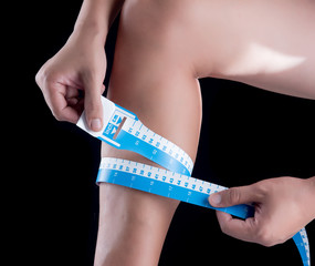 young man using measuring tape on leg over a black background.