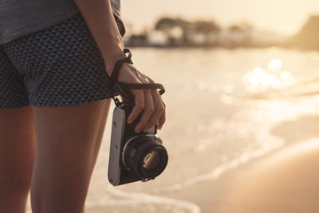 Young woman traveller with retro camera on the beach