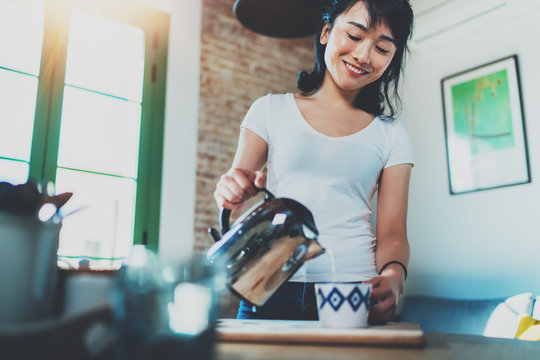 Beautiful young woman using kettle for make tea or black coffee on kitchen at living room.Women's hands pour water from a teapot into a cup. Blurred, flares effect.