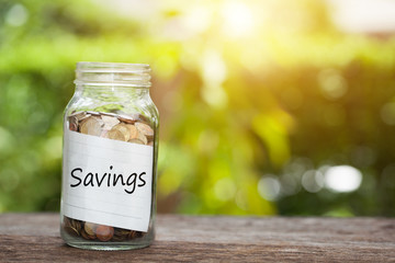 Savings word with coin in glass jar,  Business Concept.