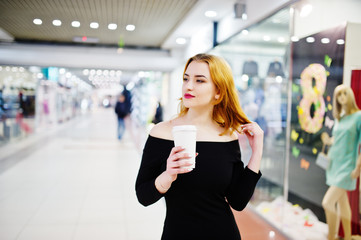 Fashion red haired girl wear on black dress with bright make holding coffee cup at trade shopping center. Photo toned style Instagram filters.
