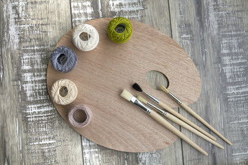 Palette with brushes and balls of cotton threads on the wooden table.