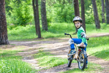 Happy cute blond kid boy having fun his first bike on sunny summer day, outdoors.  child making sports. Active leisure for children
