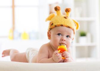 Funny baby boy in giraffe hat lying on his belly in nursery. Little kid using nibbler toy.