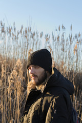 Young Bearded Man Standing Against Plants During Winter