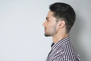 Side view of handsome young man. Beautiful profile of brunette man in checkered shirt against light grey background