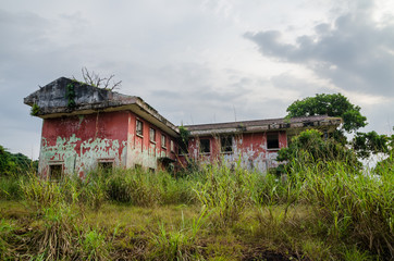 Ruined mansion surrounded by lush green with dramatic sky. Traces of the civil war in Robertsport, Liberia