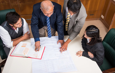 Team of Indian  or asian architects or engineers working on construction plans in the office