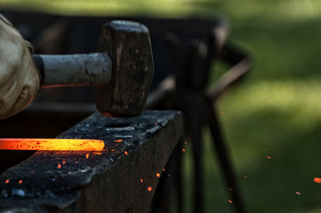 Cropped Image Of Blacksmith Hand Holding Hammer With Burning Metal