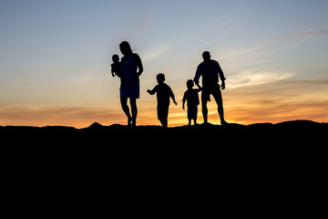 A family is silhouetted walking on a jetty at sunset.
