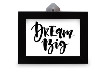 Dream big. Inspirational quote, handwritten text. Modern calligraphy. Black wooden frame. Close-up