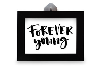 Forever young. Inspirational quote, handwritten text. Modern calligraphy. Black wooden frame. Close-up