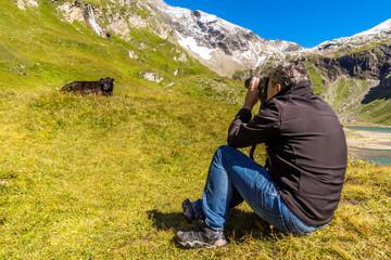 Ein Mann fotografiert eine Kuh in den Bergen