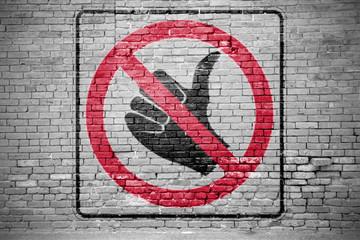 Ziegelsteinmauer mit Verkehrszeichen Kein Trampen Graffiti