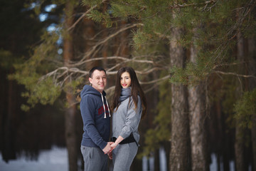 Winter snow couple love story in the forest. Happy romantic smiling lovers hugging in the snowy winter outdoors.People and love concept. Young couple of families