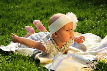 Outdoor recreation. Beautiful baby girl lying on the grass. Nature, holidays, childhood concept.