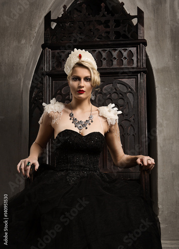 The Queen Of A Blonde Woman In A Black Dress Sits On A Wooden