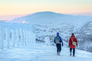 Two people hiking in snowy landscape, Finland