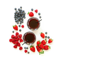 Two glasses of strawberries, raspberries, blueberries juice isolated on white.