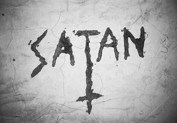 Text Satan an upturned christian cross - writing and symbol on the cracked wall. Sign and expression of satanism. Black and white pictures with dark corners