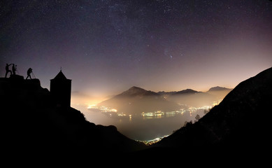 Lake of Como by night from the church of Saint Bernardo of Musso with some photographers intent on taking pictures..Church of saint Bernardo, .Musso, .Lake of Como, .Lombardy,.Italy.