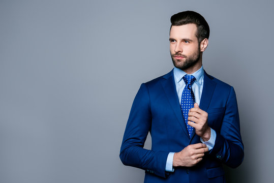Portrait of serious fashionable handsome man in blue suit and tie  buttoning cufflinks
