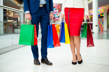 Concept of walk in  modern shopping center. close up cropped photo of handsome man in suit and stylish trendy woman in red skirt holding colored shopping packages. Young family in formal wear